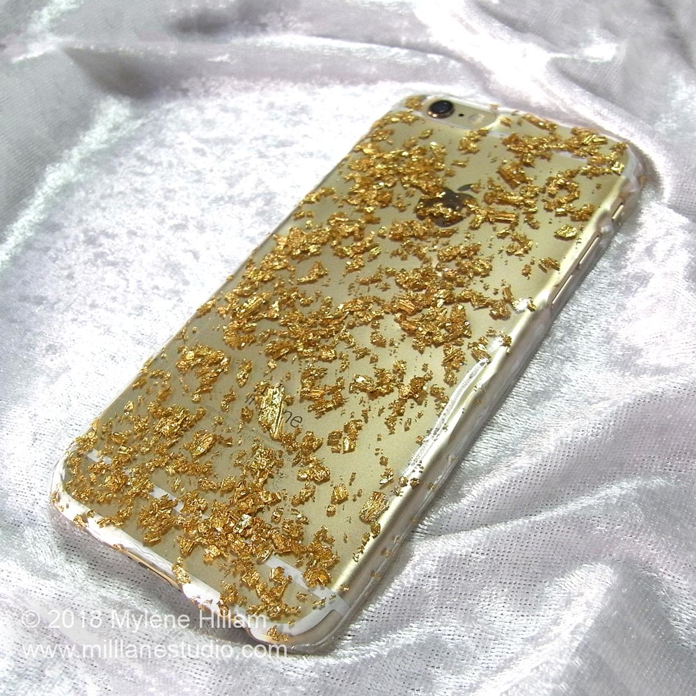 Cover a plastic mobile phone case with resin and gold leaf flakes.