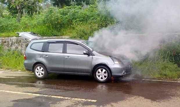 Sesaat sebelum terbakar habis, asap keluar dari kap mobil Grand Livina Kota Batu.