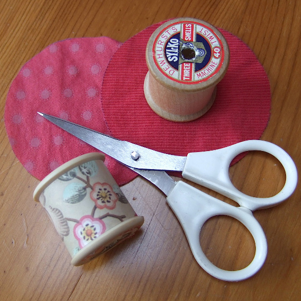 Sewing spools sharp embroidery scissors and red fabric