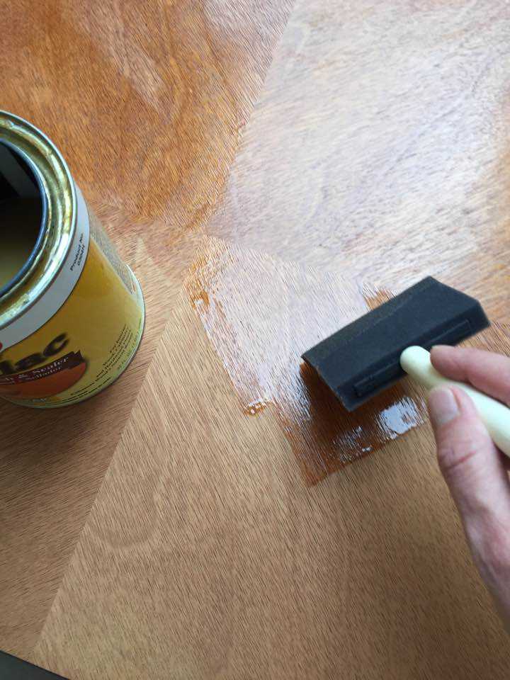 Applying shellac to raw wood before painting.