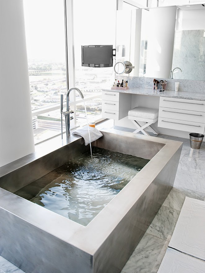 Metal freestanding tub in a white marble bathroom