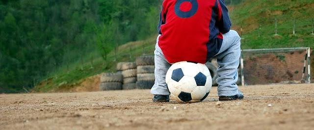 サッカーボウルの上に座っている子供