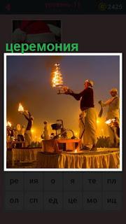 на столах стоят мужчины с огнями, происходит церемония