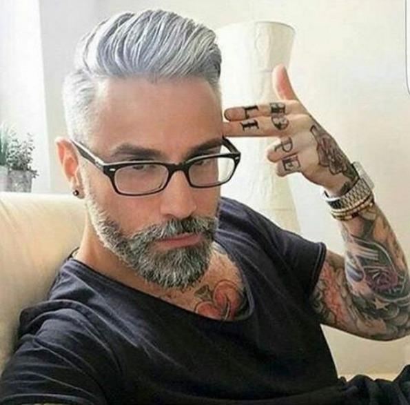 Foto de un hombre canoso y con barba con tatuajes en los nudillos