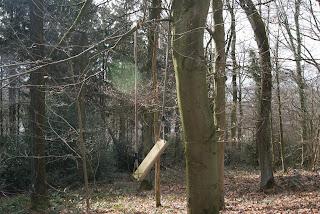 Eine Holzschaukel hängt schief an einem Ast