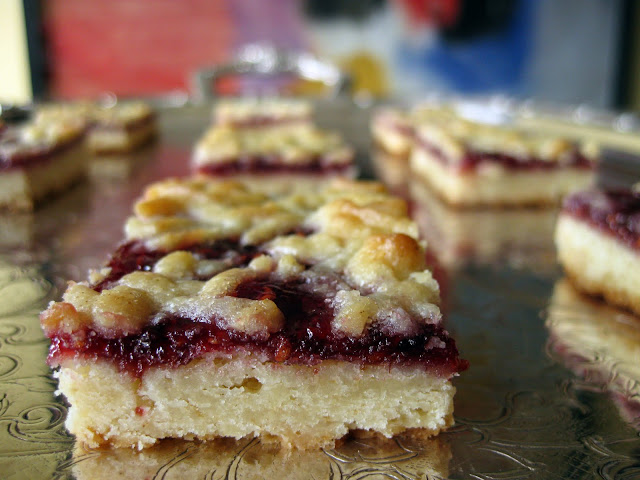 the raspberry bars are topped with a shortbread crumble