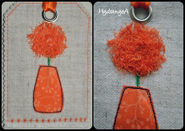 Bolsita realizada en tela para guardar ambientador armario, aplicación de un jarrón y una flor en tonos naranjas. La flor realizada utilizando el prensatelas de bucles o flecos (fringe foot)