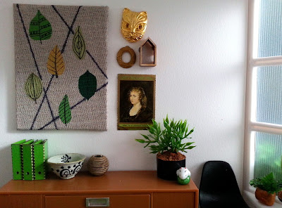One-twelfth scale modern miniature office scene containing a credenza with a black Eames chair next to it and an artwork with leaves above it. On the credenza are three green lever-arch folders, a bowl, a vase, a potted plant and a ceramic ornament.