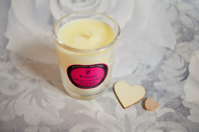 A candle with two wooden hearts beside it.