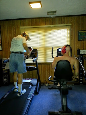 father and son both exercise and listen to music together