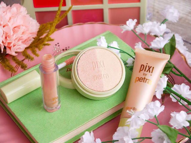 A pink plate with a green book and white faux flowers on it. On and around the book are a peachy tube of lipgloss, a tube of peach highlighter, and a round tub containing a champagne and peachy pink blush.