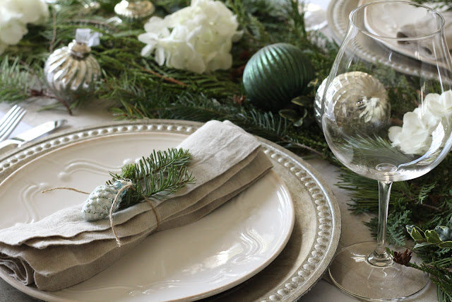 holiday tablescape with greens hydrangeas silver and white