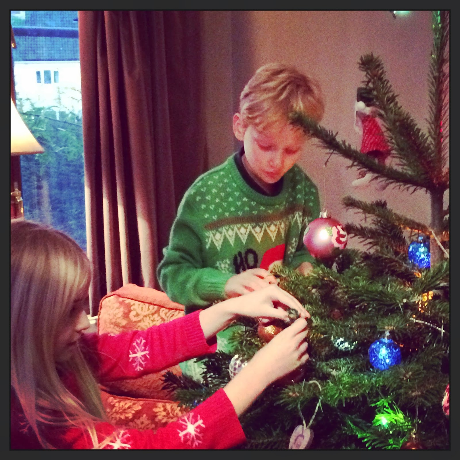 children wearing Christmas jumpers decorating tree