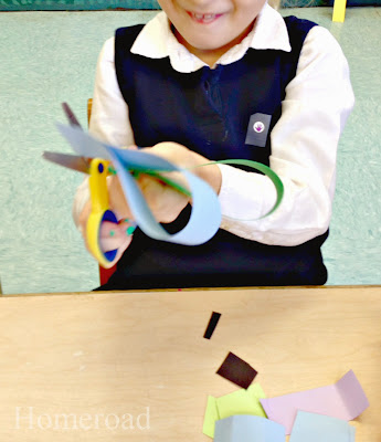 child cutting paper heart wreaths