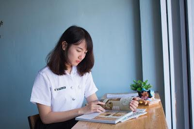 Mujer sentada a la mesa junto a la ventana, leyendo un libro, con varias revistas y una planta.
