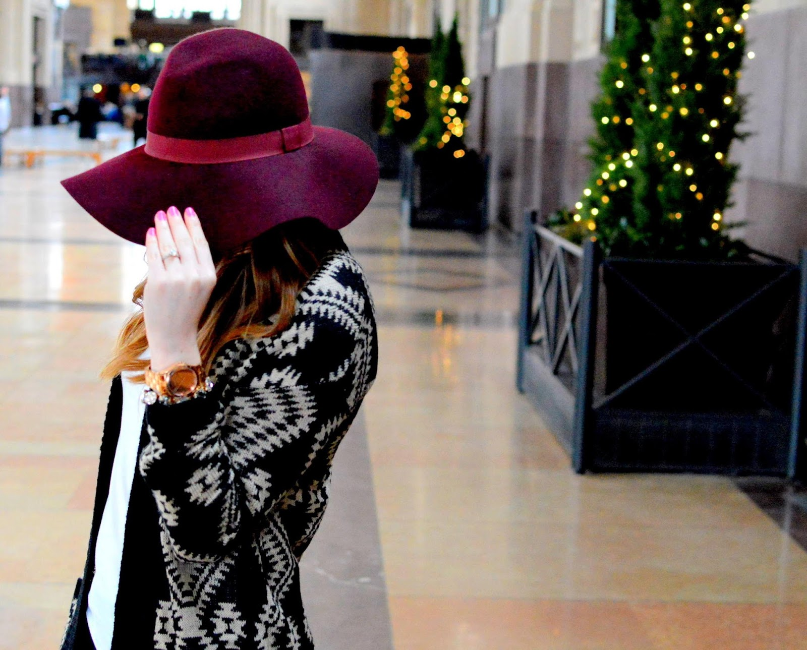 black aztec cardigan and a burgundy floppy hat