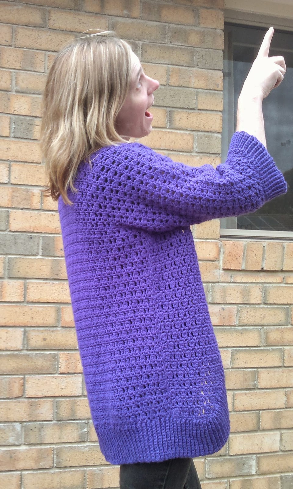 Jodie points to the sky while displaying the right hand side of the cardigan.