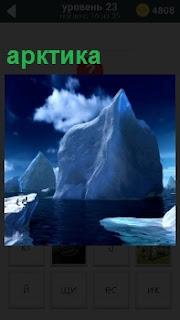 Крупный айсберг и мелкие вокруг плавают в арктике на фоне голубого неба и проплывающих облаков