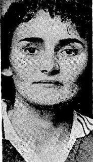 black and white picture of a woman's face, she is wearing a football shirt.