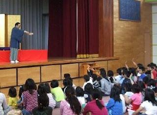親子で楽しむ小学校での三遊亭楽春の落語寄席の風景です。