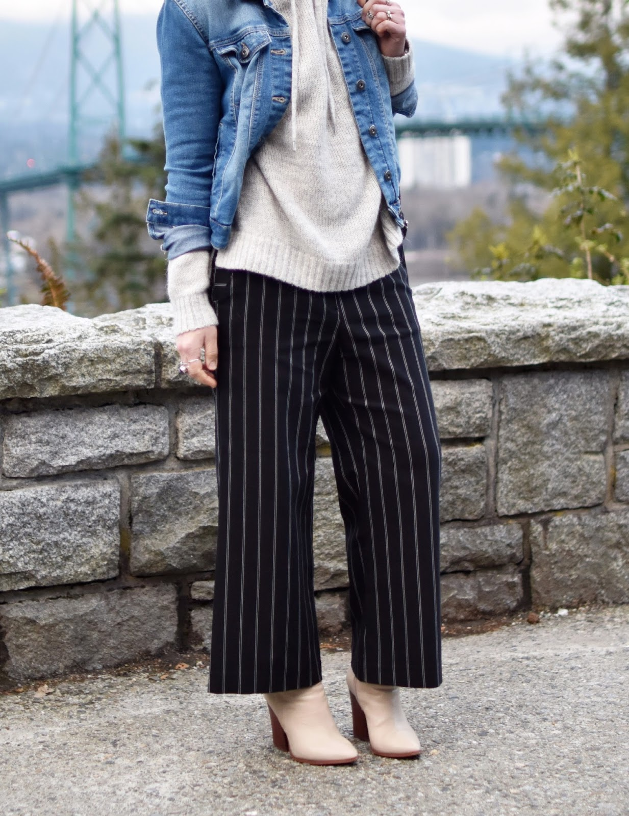 Monika Faulkner outfit inspiration -  striped cropped trousers, hoodie sweater, denim jacket, and ivory booties