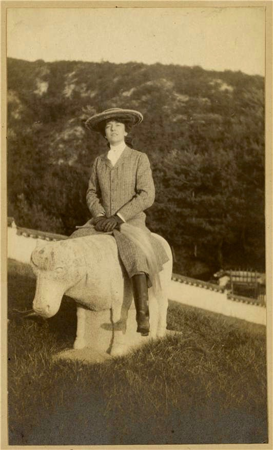 Alice Roosevelt sitting on a stone animal in Korea