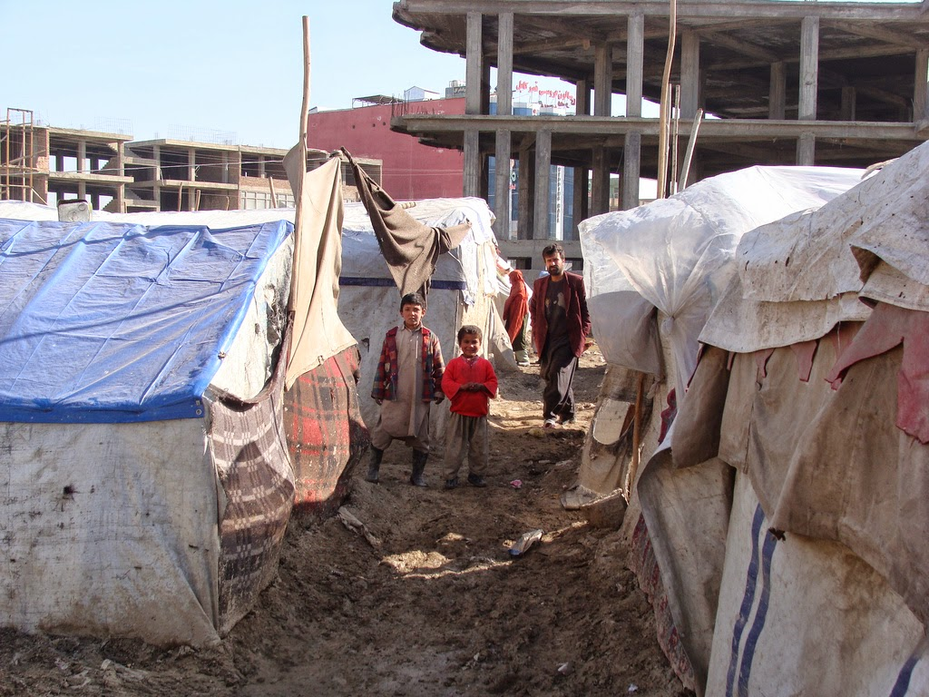 Refugees standing between refugee tents in Kabul, Afghanistan.