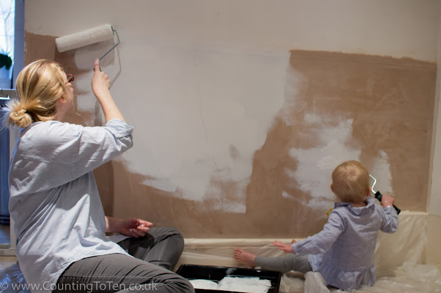 A mother and daughter in pale blue shirts painting a wall with white paint