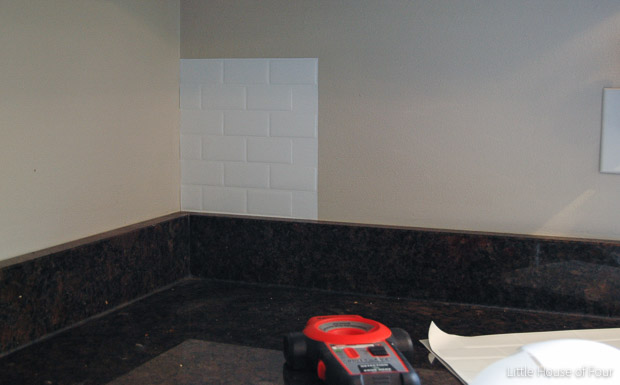 Adding peel and stick tiles to the wall