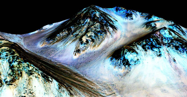 These dark, narrow, 100 meter-long streaks called recurring slope lineae flowing downhill on Mars are inferred to have been formed by contemporary flowing water. Recently, planetary scientists detected hydrated salts on these slopes at Hale crater, corroborating their original hypothesis that the streaks are indeed formed by liquid water. The blue color seen upslope of the dark streaks are thought not to be related to their formation, but instead are from the presence of the mineral pyroxene. Image Credit: NASA/JPL/University of Arizona