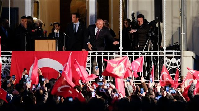 Turkish Foreign Minister Mevlut Cavusoglu addresses supporters from balcony after Germany cancels rally