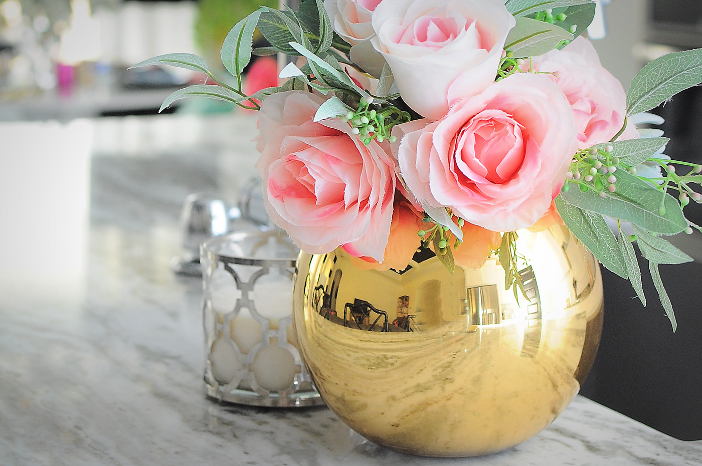 A gold vase with pink flowers looks gorgeous on a marble countertop.