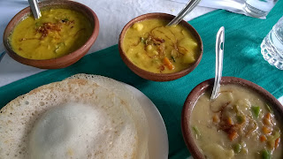 Appams, to the bottom left, served with dhal, veggie curry, and fish stew.