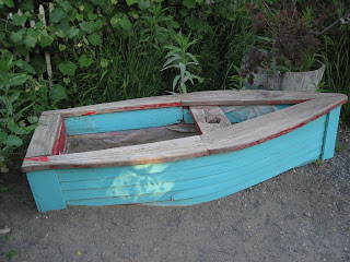 Sandbox- wooden structure shaped like a small boat, sides painted blue.