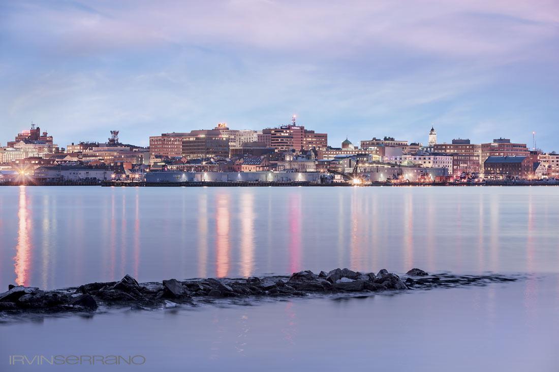 Portland Maine's city skyline sparkles over Casco Bay at dusk.