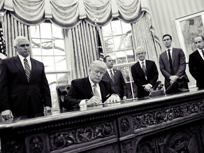 President Donald Trump signs executive orders in the Oval Office.