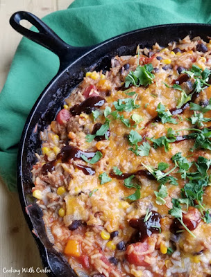 close up of skillet full off bbq pulled pork, rice, black beans, corn and melted cheese