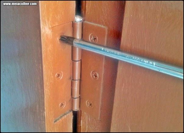 tirando a dobradiça da porta de madeira com chave