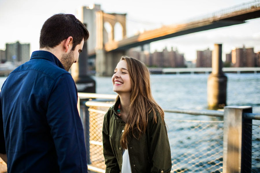 Candid laughing engagement portraits with brooklyn bridge NYC skyline in background - www.cassiecastellaw.com