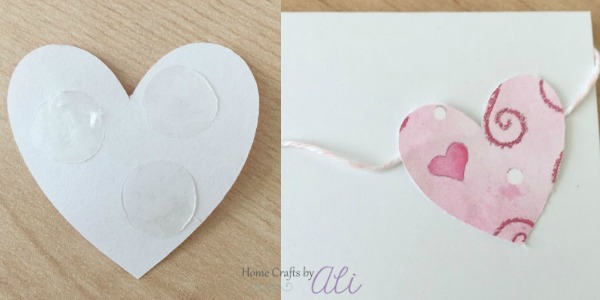 use glue dot adhesive to add paper cut out hearts to the banner