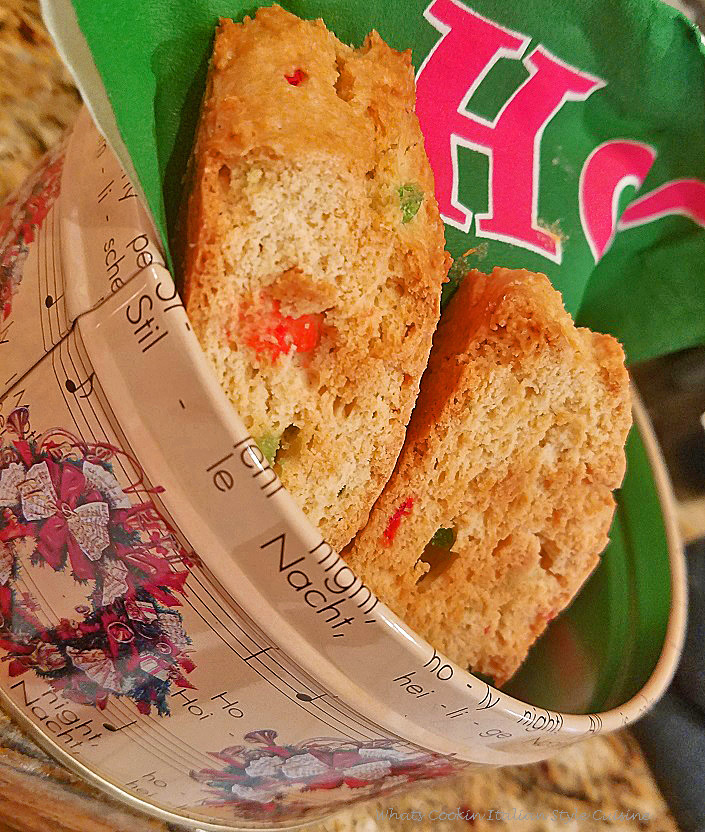 These are biscotti cookies that are anisette flavored with green and red cherries for Christmas in a pretty tin that has silent night and other musical staff songs on the tin. There is a green napkin in the tin with the cookies on top.