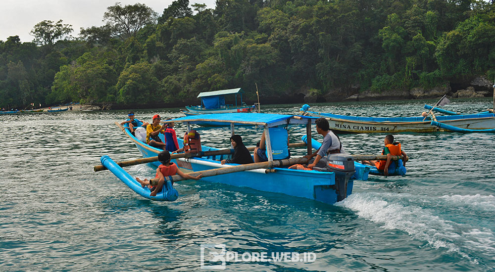 menggunakan perahu wisata berkeliling Pangandaran