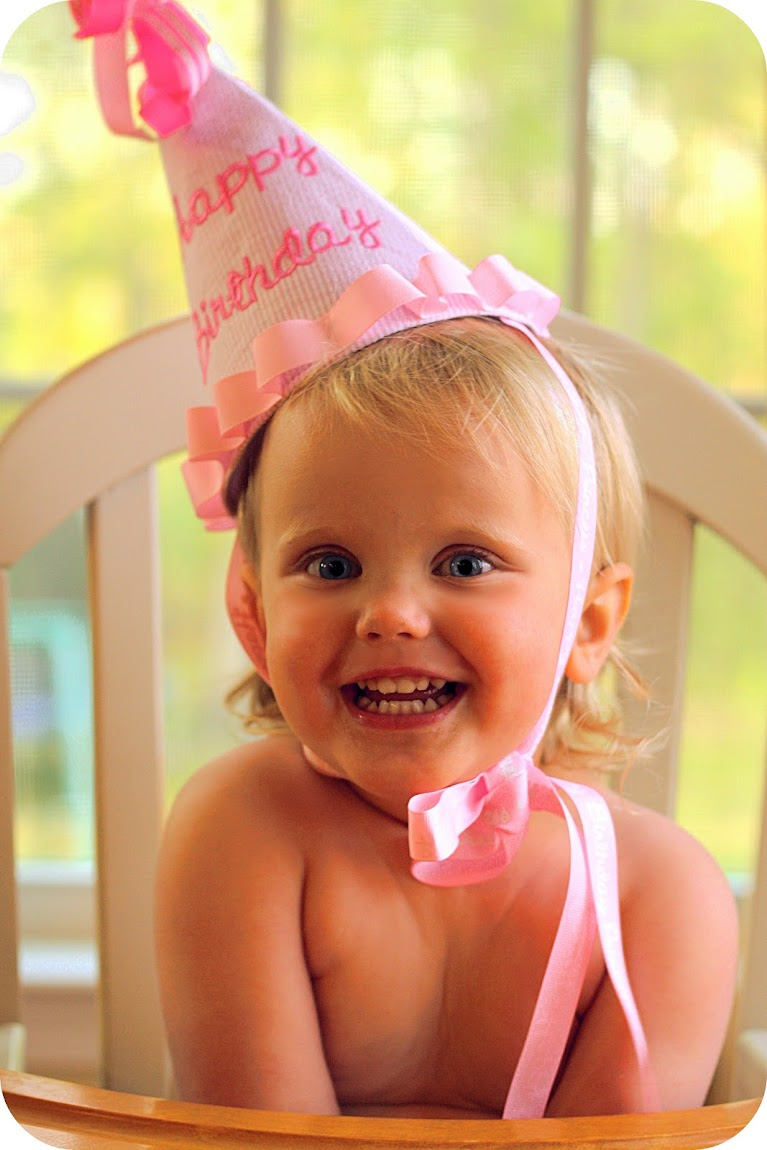 pink birthday hat on a chunky little girl