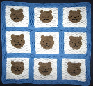 A square baby blanket made up of 9 squares, joined by blue borders. Each square is white with a tan circle in the middle. The circle is a teddy bear's face. Facial features are embroidered in black yarn. The ears are shaped like half circles and stitched on to the surface of the blanket along the top edge of the tan circles so that they can flap about. The blanket resembles a tic tac toe game except there are faces where the noughts and crosses should be and the entire blanket is finished off with a plain blue border of solid crochet around the perimeter.