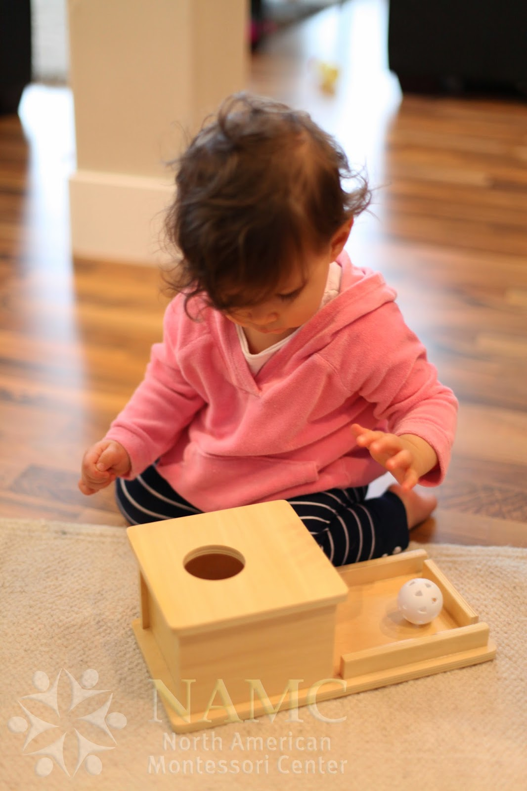 NAMC Montessori developing object permanence girl with box and ball