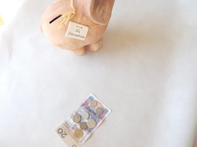 """Oszczędności wrzucane do skarbonki i skarbonka z napisanym celem """"na szczęście"""""""