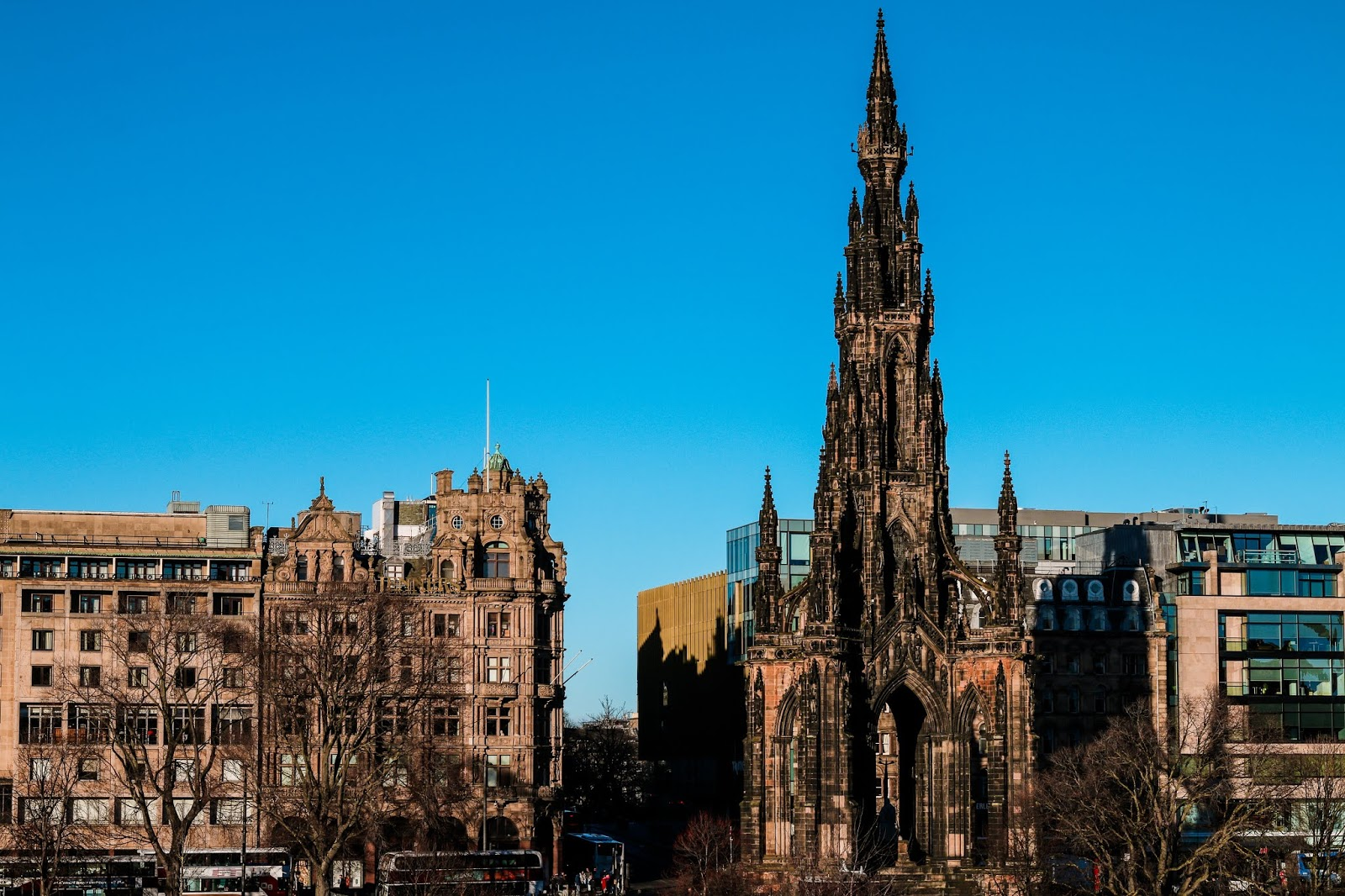 a landscape photo of Edinburgh that shows some buildings in the distance and a blue sky