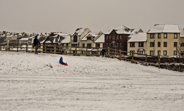 Photo of a child sledging near Maryport harbour