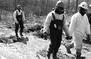 workers wade thru toxic mud at Trumbull County, Ohio fracking waste  injection well spill, Vienna , Ohio