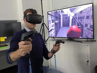 seorang pria memainkan virtual reality lengkap dengan remote dan layar untuk demo
